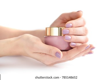 Hands of a woman with pink manicure with jar of cream on white background
