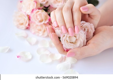 Hands of a woman with pink manicure on nails and roses