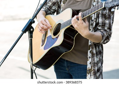 hands of woman playing the acoustic guitar at street concert