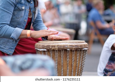 The hands of a woman playing on an African djembe drum, at a percussion music festival