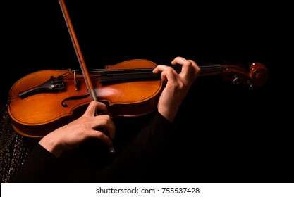 Hands of a woman playing the violin isolated on black background