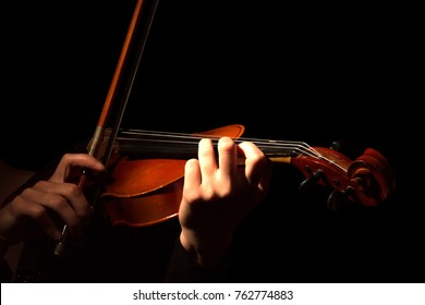 Hands of woman playing violin isolated on black background