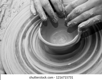 Hands of woman in process of making clay bowl on pottery wheel. Potter at work. Black and white toned image.