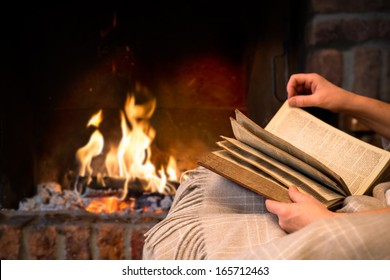 hands of woman reading book at fireplace