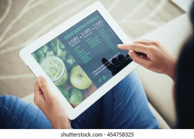 Hands of woman reading smoothie recipe on website
