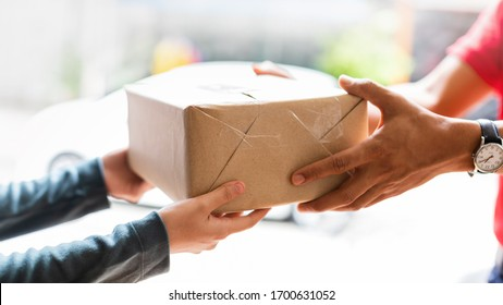 Hands of woman receiving parcel. Delivery man service sending boxes product at the door. Express delivery service. Online shopping at home.
