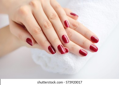 Hands of a woman with red manicure are on a towel