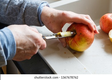 Hands of a woman removing an apple core with an apple corer in a kitchen