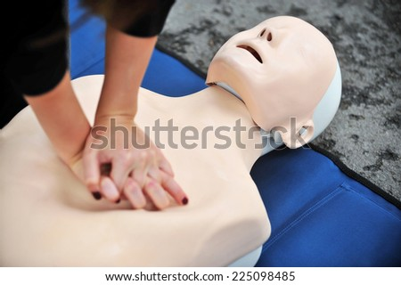 Hands of a woman are seen on a mannequin during an exercise of resuscitation