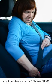 Hands of a Woman Sitting In the Car Fastening Seat Belt. A senior woman enjoys a newly acquired car with modern systems of active and passive safety, navigation of voice commands.