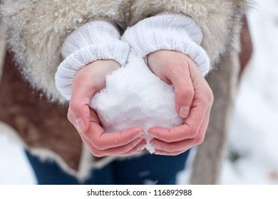 Hands of woman with snow heart in winter