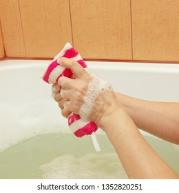Hands of woman soaping a striped sponge in the bathroom