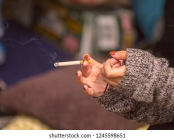 Hands of a woman in a sweater holding a burning tobacco cigarette. Indoor home setting.