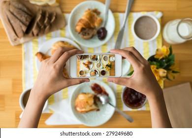 Hands of woman taking photo of her breakfast