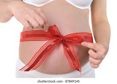 hands of  woman tied  red ribbon around  her pregnant belly