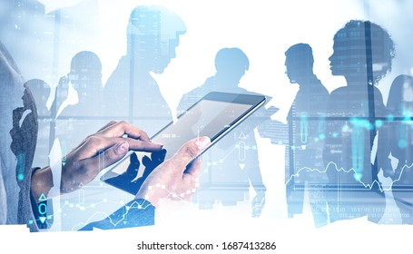 Hands of woman trader using tablet computer in blurry office with double exposure of digital graphs and night cityscape with diverse business team. Concept of stock market and teamwork. Toned image