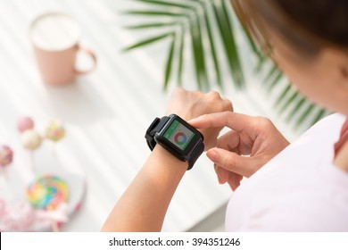 Hands of woman using application on her smart watch