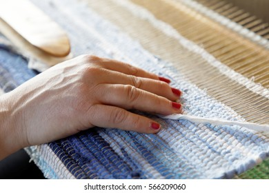 Hands of a woman when weaving a blue and white rag carpet in the loom
