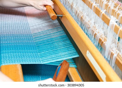 Hands of a woman who weaves on a loom