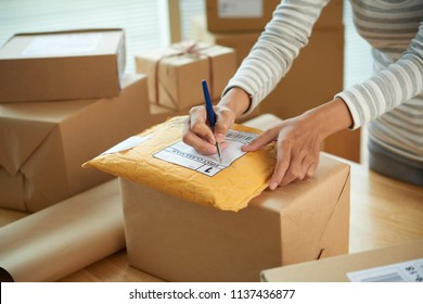 Hands of woman writing address on fisrt class package with goods