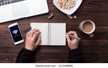Hands of woman writing in the notebook while connecting wifi on smartphone with wooden desk background