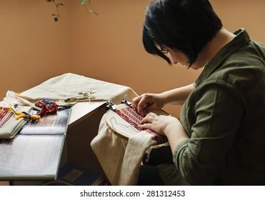 Hands women embroider on embroidery frame (cross stitch)