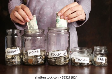 Hand's women putting coin in money jar with text . Concept of investments, insurance, savings plans.