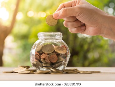 hand's women putting golden coins in money jar. concept of banking, finance and savings.