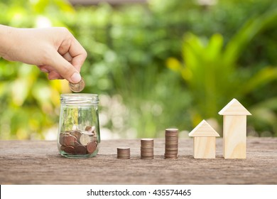 Hand's women putting golden coins in money jar. Concept of real estate investments, Home insurance, Savings plans for housing. , The concept of financial savings to buy a house.