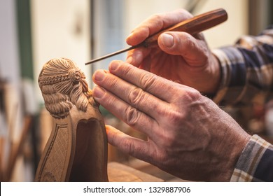 Hands of a wood sculptor working on a small wooden figure