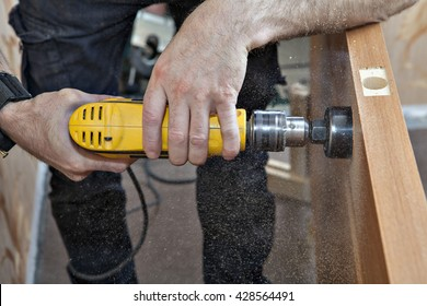 Hands woodworker with yellow electric drill, boring large hole of door lock, using hole saw drill bits, sawdust flying around, close-up.