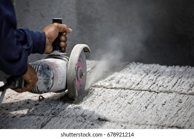 Hands of worker catching and using electric cutting machine tool to cut concrete floor with dirty dust spreading in air, copy space on the right.