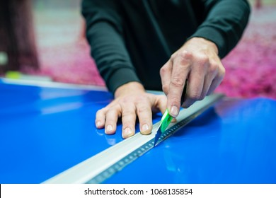 Hands of a worker cutting with a cutter and a ruler, a blue vinyl