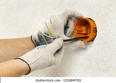 hands of an worker fastens the socket box on the wall