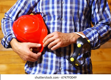 Hands of worker with helmet.