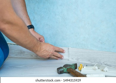 Hands of worker instal plastic skirting board on laminate flooring. Renovation of baseboard at home.