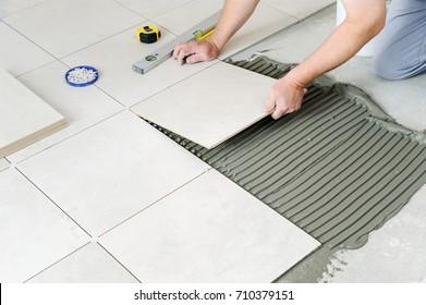 Die Hände des Arbeiters legen die Keramikfliese auf den Boden.