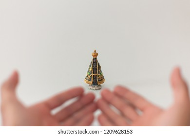 hands of a worker in position of supplication in front of an image of a Catholic saint, Our Lady Aparecida.