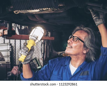 Hands of a worker repairing car service.