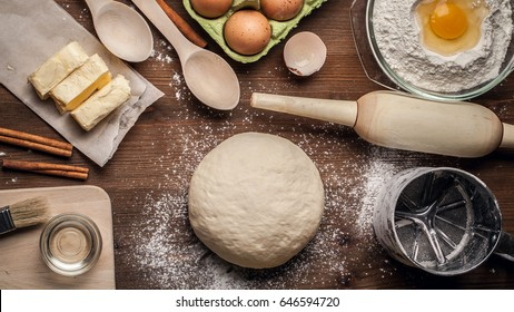 Hands working with dough preparation recipe bread, pizza, pie or samsa making ingridients, food flat lay on kitchen table background. Butter, milk, yeast, flour, eggs, sugar pastry or bakery cooking