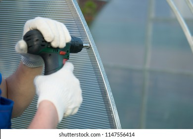 hands working with gloves, using an electric screwdriver connect the polycarbonate to the frame of the greenhouse