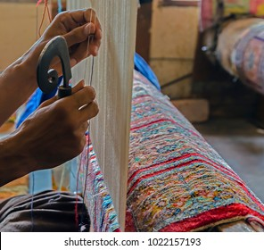 Hands working at one persian carpet inside in the manufacture from Srinagar, Jammu and Kashmir, India.