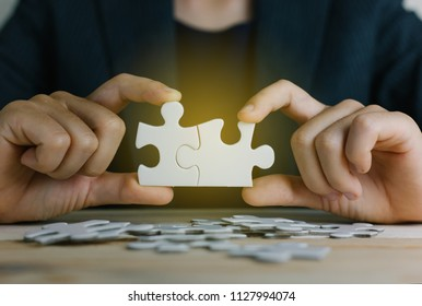 Hands of working woman connecting jigsaw puzzle with light effect, Business solutions, success and strategy concept