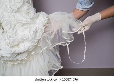 Hands works in bride dress repair