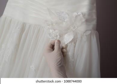 Hands works on wedding dress repair