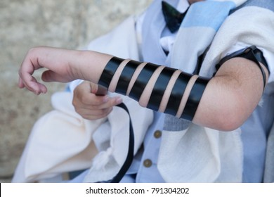 Hands wrap tefilin around the arm with the Kotel in background. Jewish teenager 13 years old  celebrates bar mitzvah at the wailing wall and praying with hands on the stones