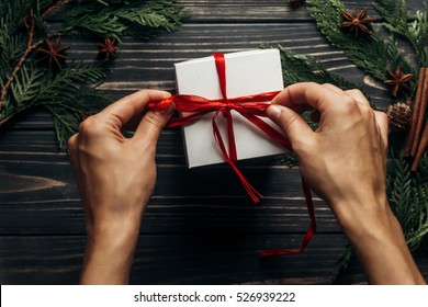 hands wrapping christmas present with red ribbon on stylish wooden background flat lay with green branches. space for text. greeting card concept. seasonal greetings for winter. shopping holidays