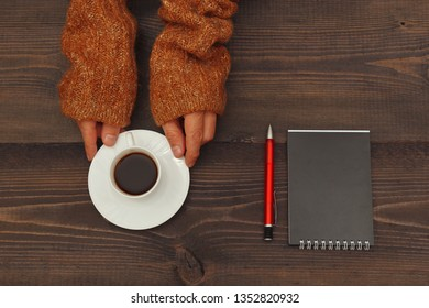 Hands of writer with a cup of coffee at a wooden table with a notebook and pen