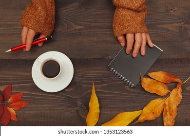 Hands of writer with a pen and notebook at a wooden table with a cup of coffee and autumn leaves