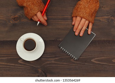 Hands of writer with a pen and notebook at a wooden table with a cup of coffee